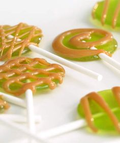 Easy Caramel Apple Lollipops | We whipped up our own adorable version of one of our childhood favorites with these caramel apple lollipops. Start with green apple flavored hard candies (we like Jolly Ranchers). Melt them slowly in a medium pot, but watch carefully: you don't want them to take on any color. Pour the melted candy onto a silicone baking mat, then gently lay a lollipop stick on top.