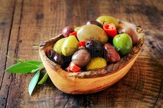 Assortment of pitted olives in brine in a rustic wooden bowl Stock Photo