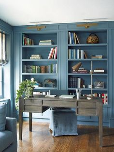 This home office room enjoys blue palette amongst a neutral foundation of natural wood grain flooring.