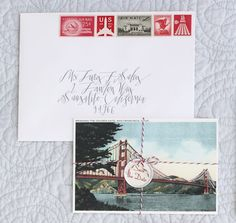 love the vintage postcard, calligraphy and stamps for these wedding invitations