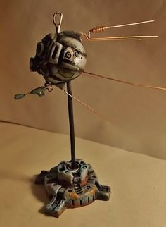 Eyebot Mixed Media MultiDisplay This art piece has the ability to be suspended (as in, it can be worn on a chain or hung with fishing line) as well as displayed on a pedestal base, which is included. The antennae are removable, and thus their positioning can be changed.  SailerFineArt on etsy.com