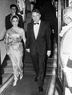 "Elizabeth Taylor and Richard Burton at the Lido Nightclub in Paris, 1964. Liz's hair style was inspired by a 16th Century Indian painting, and adorned with a brooch given to her by Richard Burton while filming ""The Night of the Iguana""."