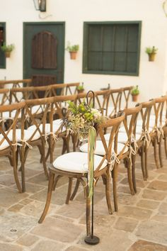 wood chairs and hanging floral ceremony decor