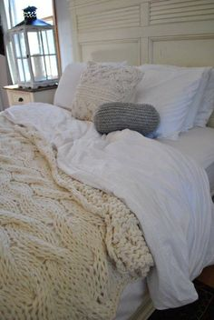 .This cozy, natural, crocheted, cable-knit blanket