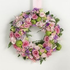 This wreath is made up with a combination of pink roses, pink carnations, lavender stock, pink spray roses, pink and green gladiolus, green hydrangeas and the clever addition of green apples.