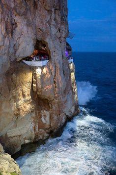 Cova den Xoroi bar in Cala en Porter, Menorca, Spain, nighttime.