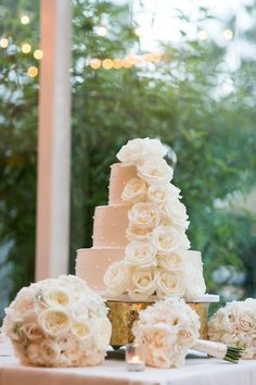 Keep your wedding cake traditional but breathtaking with a tiered white wedding cake adorned in roses and pearls.