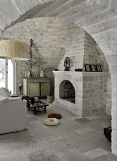 Love the curved ceiling and archway, the white brick, it's like a chic hobbit house!