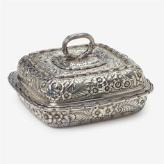 """Sterling silver covered entrée dish Tiffany & Co., New York, NY, 1873-91 Shaped square form with scalloped edge, heavily repoussé and chased with floral blossoms and foliage throughout, underside engraved with """"EDLH"""" monogram for Emilie Duval Lee Herreshoff (1863-1920)."""