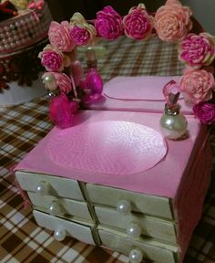 This mini dressing table made up with only waste material.. I made its flowers from sola wood. .. and drawers from empty match boxes and tiny pearls looking like perfume bottles by Monika Singh..