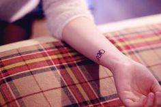 Wrist tattoo of a small ribbon by Seoeon. Love Tattoos, Small Tattoos, Tattoos For Women, Ribbon Bows, Ribbons, Ribbon Tattoos, Temporary Tattoo Designs, Wrist Tattoo, Tattoo Artists