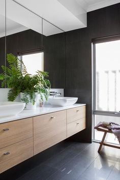 Colours and materials in the bathroom reflect the kitchen palette for a cohesive result. Cabinetry in Laminex Sublime Teak with Essastone surface.