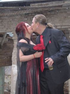 gothic bride is kissing her groom