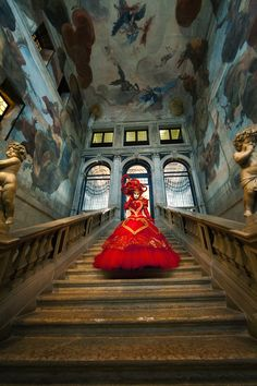 Carnival model in red walking down a beautifully painted staircase