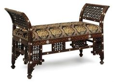 A Syrian Mother-of-Pearl and bone inlaid hardwood bench, first half century. Carved overall and divided by panels of mashrabiya, the upholstered seat covered in Robert Kime Ltd.