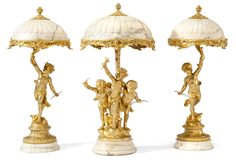 A Very Fine French 19th/20th Century Gilt-Bronze and Alabaster Three-Piece Figural Garniture Lamp Suite, by Jean-Louis Gregoire (French, 1840-1890), one centered by a figural group of three putti at play, two in the form of a single figure, holding aloft a foliate spray supporting the domed alabaster shades, on circular feet. Signed: Gregoire. Circa: Paris, 1900.