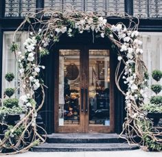 Branch-y arch with floral and topiaries via Joie Instagram