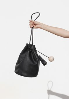 Bucket in Pebbled Black a classic bucket bag 32 × 21 cm, strap drop 33 cm  $485.00  Pebbled black leather, Rubber shoulder strap, Leather tassel and wood sphere, Leather lined base