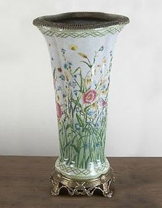 Add enchanting style to any room in your home with the stunning Cora Porcelain Vase with Bronze Base and Rim that features a delicate botanical motif and shining bronze base.
