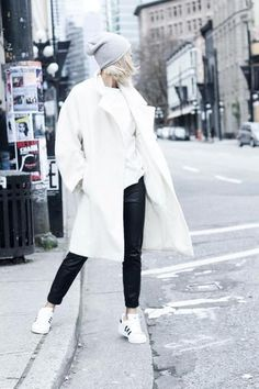 Street Style: Black and white winter outfit. Leather pants, black and white Adidas worn with an oversized white coat.