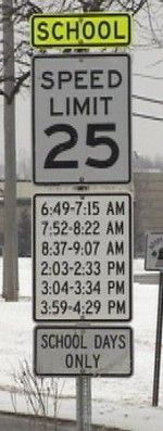 What? How many accidents happen here, while drivers are looking at their clocks to see what time it & trying to figure out where that time is on this sign???