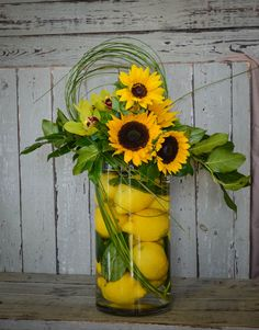 Citrus is in! Lemons, sunflowers and orchids with bear grass in a cylinder vase. Elegant & cheerful.