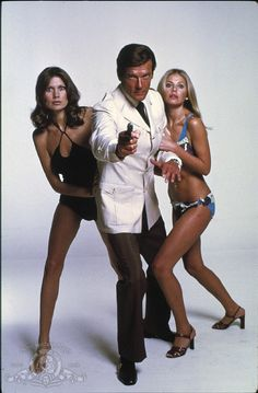 Roger Moore with Maud Adams and Britt Ekland from the James Bond 1974 film, The Man with the Golden Gun. Whatever their role, Bond girls still must be inarguably beautiful. James Bond Women, James Bond Actors, James Bond Movie Posters, James Bond Movies, Britt Ekland, Roger Moore, Sean Connery, Monsieur Cinema, Bond Series