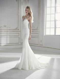 Elegante, sensuale e romantico. Questo abito da sposa a sirena, a vita bassa, dal corpetto con trasparenze, si fonde con la silhouette. Il modello slancia l