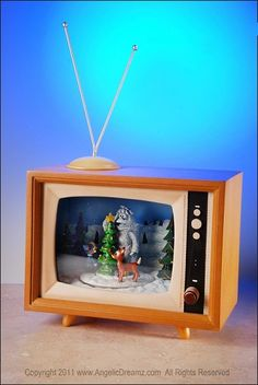 "Roman Inc.  6.7"" Rudolph TV with Motion & Music  Materials: Resin/Plastic/WIre  Size: 6.75""H x 8.5""W x 5.125""D    Watch Rudolph and his friends revolve in this adorable retro TV! Plays eight various Christmas songs at the touch of a button.    Your Price: $125.00"