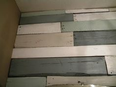 Pallets painted in four different colours to make a wall: white, pale coffee, pale green and grey