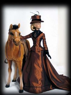 A Victorian riding habit of rust and black shot silk taffeta. Black velvet accents as a collar and cuffs., with silky black soutache trim. Sydney is ever so splendid in this regal ensemble.