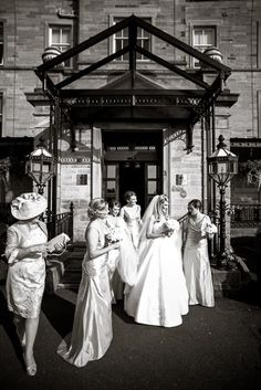 Bridal party walking outside to their wedding transportation, black and white color photo