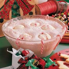 "Candy Cane Punch - Peppermint ice cream makes this beverage taste—and look—more like a dessert than a punch! I had this at a party last week, and I could NOT stop! OH MY GOODNESS! SO DELISH! ""It's a great way to start a gathering."" For a fun garnish, you can hang mini candy canes around the punch bowl and cups."