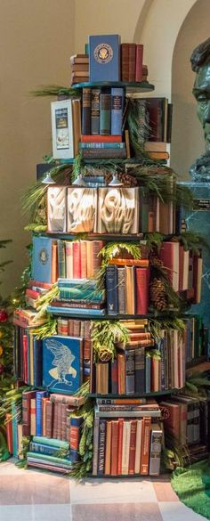 "The W.H. East Garden Room, known as ""Booksellers,"" showcases stacked books that creatively form a Christmas tree."