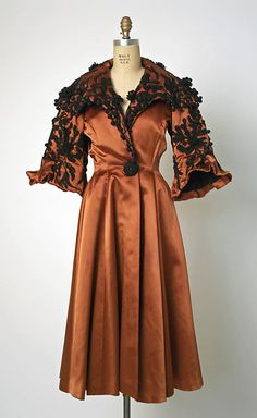 Late-1940s Evening coat. Russet silk and wool satin weave. Portrait collar, fit-and-flare shape, wide elbow sleeves with flounce ends, and ornate dark soutache on top. By Balenciaga. Photo: Metropolitan Museum of Art.