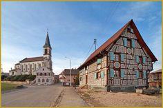 Photo à la sortie de l'hiver d'une maison alsacienne à colombages de 1832, de l'église Saint-Jacques-le-Majeur et de la mairie de Michelbach-le-Haut. Photos de Michelbach-le-Haut, visiter le Sundgau, tourisme en Alsace.