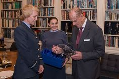 Cadet Sergeant Bronwyn Jacobs (centre) stands with the Duke of Edinburgh as he is presented with a gift of a crystal vase from Air Commodore Dawn McCafferty  (left)