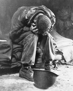 A young American GI shows the fatigue of battle as he weeps at a battlefront collecting station after heavy fighting