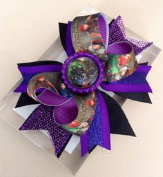 Boutique Style Descendants Hair Bow.  • Measures approximately 4 3/4 across • Printed Descendants ribbon • Alligator clip • All ribbon ends are heat sealed to prevent fraying. • Matching bottle cap • Colors can be customized , please contact me if you have any questions.