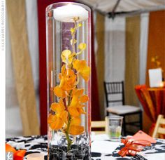 Submerged bundles of orchids and calla lilies were placed in clear vases on the tables. White floating and votive candles along with black pebbles on the tables added the feel of fire and water to the couple's earthy theme.