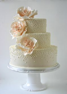 Gold, tan, ivory, white, tiny polka dot ombre round wedding cake, with large peach open icing peonies flower.