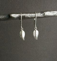 Perfect everyday sterling silver earrings. Light weight and beautiful, simplicity at its best! Tiny leaf charms made from sterling silver dangle below sturdy and secure sterling silver lever back ear wires. These petite earrings measure a little over 1 in length in total. These