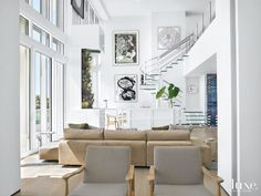 STATEMENT STAIRCASE...The free floating-step staircase is complimented by paintings by Richard Serra and Frank Stella from Evelyn Aimis Fine Art that form a vertical gallery above the sideboard in this modern Miami Beach great room.  Photography: Troy Campbell