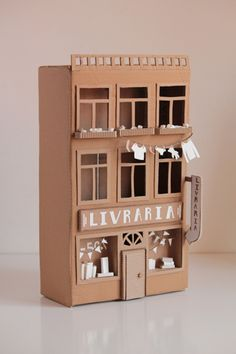 Cardboard book shop (Livraria) -- a small decorative house inspired by Portuguese buildings in Porto, made with used cardboard boxes. This book shop (in Portuguese: Livraria) was part of the mock-up of a life-size project.