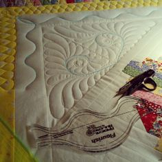 Feather quilting by Elizabeth Karnes , love the overlap of the ruler for the spine in the corner.