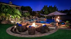 This backyard oasis from designer Nick Martin features a crystal clear pool surrounded by lush tropical vegetation. Water features within the pool create a sense of motion while stone tile pavers create a natural hardscape. A fire pit area with wicker chairs is great for cooler nights.