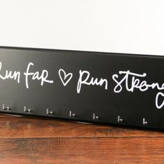 """Proudly display all your race bling on our exclusive medal holder. We've collaborated with Strut Your Stuff Sign Company to offer the """"Run Far, Run Strong"""" medal holder. Available in 12 different colors you can customize the look of your medal holder. $42.50 Order directly from Strut Your Stuff Sign CompanyHERE."""