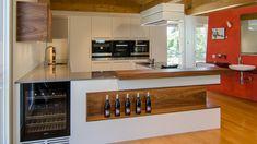 Raffinierte, beleuchtete Nische in amerikanischem Nussbaum. Daneben ein Weintemperierschrank der Firma Miele mit zwei Kühlzonen.