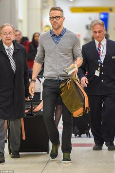 Studious: On Friday Ryan Reynolds had his muscles under wraps as he arrived at New York's JFK airport