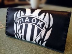 This is an order from a football fan  Tobacco pouch in black GENUINE leather. The drawing displays a football team's logo. It has pockets for filters and rolling papers. It closes with magnetic stads.  Dimensions: 150mm x 200mm.